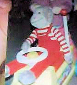 Large Gray Monkey Wearing Red Overalls and Red Striped Long Sleeved Shirt