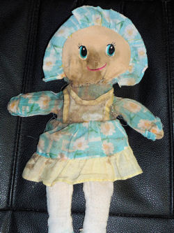 Rag Doll Wearing a Blue Dress & Bonnet with White Flowers & Yellow Trim