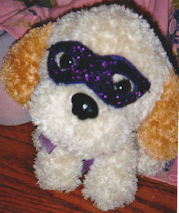 White Seated Dog with Orange Ears Wearing a Purple Sequinned Mask