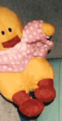 90's Puffalump Style Yellow Duck with White Hair Tuft wearing a White Polka Dotted Pink Dress